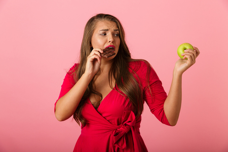 Image of a confused young woman isolated over pink wall background holding chocolate and apple. Stock Photo - 113602320