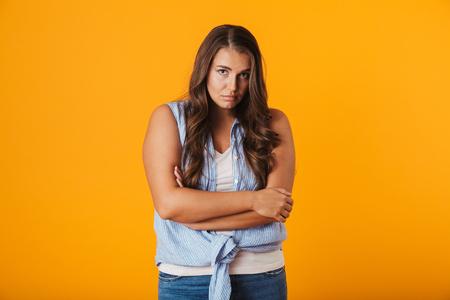 Sconvolto giovane donna in piedi isolata su sfondo giallo, tenendo le braccia conserte