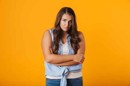 Upset young woman standing isolated over yellow background, holding arms folded 스톡 콘텐츠