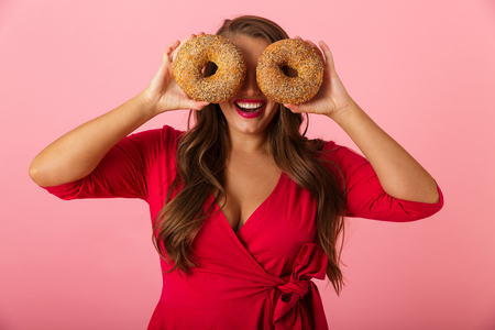 Image of a happy young woman isolated over pink wall background holding donuts covering eyes. Stock Photo