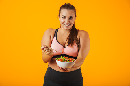 Image of big sportswoman in tracksuit eating green salad from plate isolated over yellow background