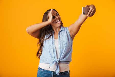 Cheerful young woman standing isolated over yellow background, taking a selfie with outsretched hand