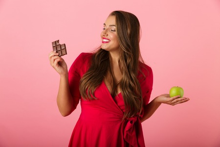 Image of a beautiful hungry young woman isolated over pink wall background holding chocolate and apple.