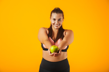 3d86896857 Portrait of attractive chubby woman in sportive bra holding apple isolated  over yellow background