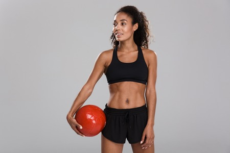 Image of amazing young strong sports woman make exercises with ball isolated.