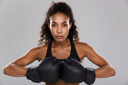 Portrait of an afro american confident young sportswoman doing boxing isolated over gray background, looking at camera