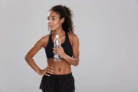 Portrait of a smiling young african sportswoman resting after training isolated over grey background, holding bottle with water