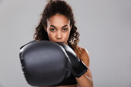 Portrait of an afro american smiling young sportswoman doing boxing isolated over gray background, punching camera Stockfoto