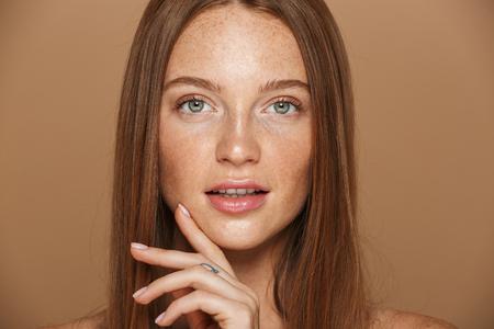 Schoonheidsportret van een sensuele jonge vrouw met lang rood haar die zich voordeed, hand in hand op haar gezicht geïsoleerd over beige achtergrond