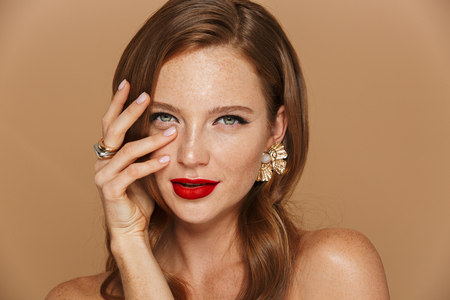 Close up of a beautiful young woman wearing makeup and jewelry accessories posing isolated over beige background, holding hand at her face Stock Photo