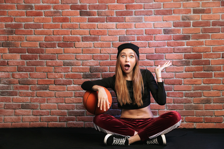 Photo of attractive sporty girl 20s sitting on floor against brick wall with basketball Banque d'images