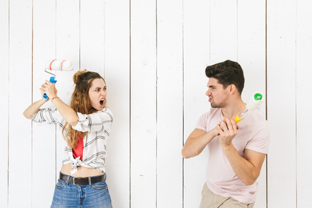 Image of amusing couple man and woman painting white wall and making renovation using paint rollers Banque d'images - 113607631