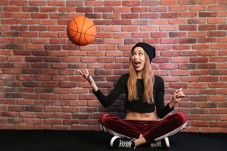 Photo of pretty sporty girl 20s sitting on floor against brick wall and playing with basketball