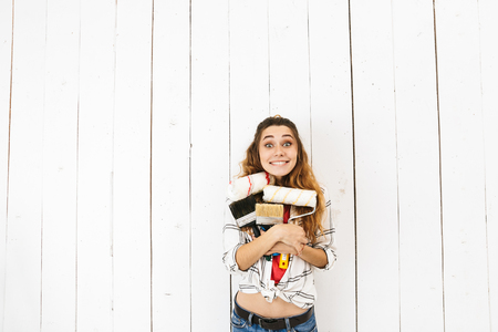 Portrait of happy girl 20s holding roller and brush while painting white wall