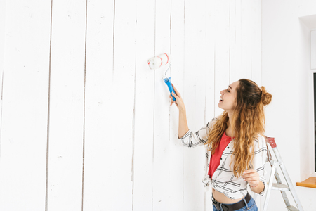 Image of brunette woman 20s painting white wall and making renovation using paint roller