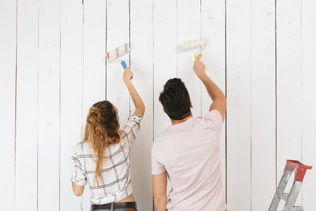 Photo of caucasian couple man and woman painting white wall and making renovation using paint rollers Banque d'images - 113609533