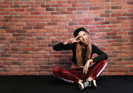 Photo of teenage hip hop dancer or sporty woman sitting on floor against brick wall