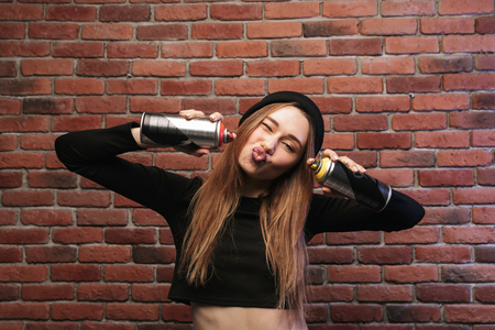 Portrait of caucasian hip hop girl 20s standing against brick wall with spray cans