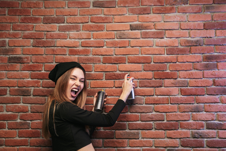 Image of stylish hip hop girl 20s drawing on brick wall with spray paint