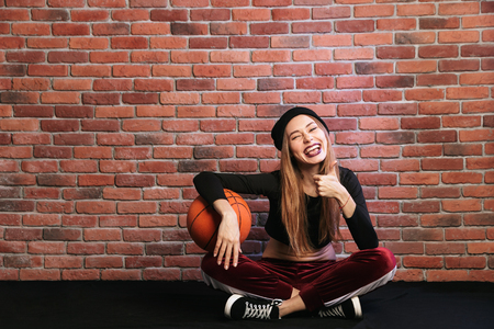 Photo of delighted girl 20s sitting on floor against brick wall and holding basketball