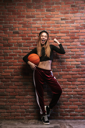 Full length portrait of seductive girl 20s playing basketball against brick wall