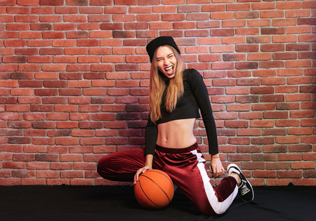 Photo of excited girl 20s sitting on floor against brick wall and holding basketball Stockfoto