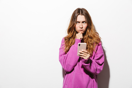 Portrait of resentful woman 20s wearing sweatshirt holding mobile phone while standing isolated over white background