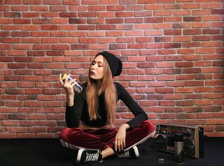 Photo of modern hip hop girl sitting on floor against brick wall with boombox and spray paint