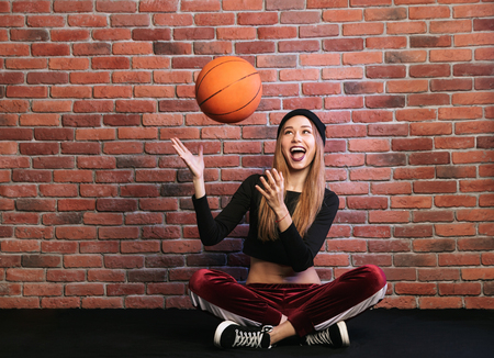 Photo of teen sporty woman 20s sitting on floor against brick wall and playing with basketball