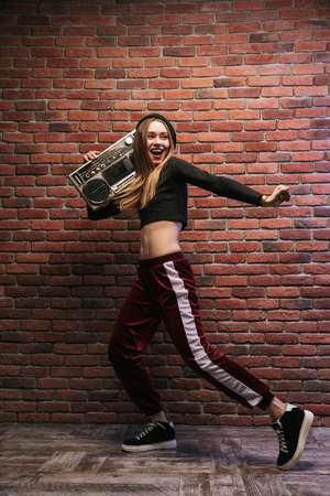 Full length image of subcultural woman 20s standing against brick wall and holding boombox