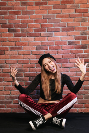 Photo of trendy hip hop dancer or sporty woman sitting on floor against brick wall