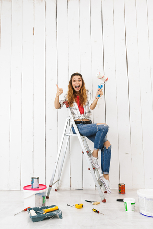 Full length photo of european woman 20s sitting on ladder and painting wall during renovation at home Banque d'images - 113665487