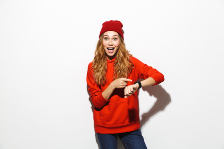 Portrait of an excited girl wearing hoodie isolated over white background, showing wrist watch