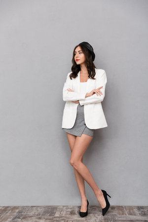 Full length portrait of a pretty young woman dressed in mini skirt and jacket standing over gray background, looking away Imagens