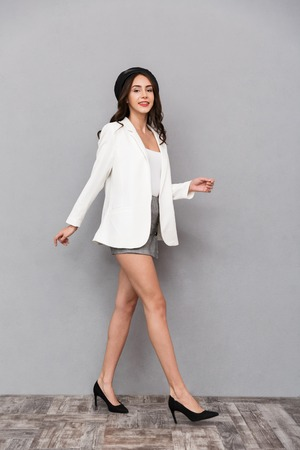 Full length portrait of a pretty young woman dressed in mini skirt and jacket walking over gray background, looking at camera