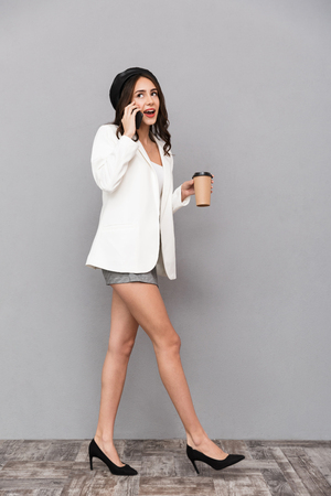 Full length portrait of a cheerful young woman dressed in mini skirt and jacket over gray background, holding cup of coffee, talking on mobile phone, walking Standard-Bild