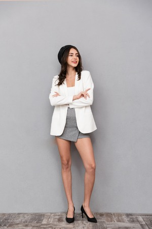 Full length portrait of a beautiful young woman dressed in mini skirt and jacket standing over gray background, looking away Stockfoto