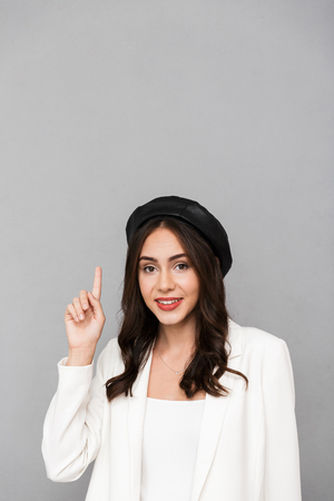 c7d74c22c26 Portrait of a smiling young woman wearing beret standing isolated over gray  background