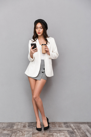 Full length portrait of a beautiful young woman dressed in mini skirt and jacket over gray background, holding cup of coffee, using mobile phone Imagens - 115344718