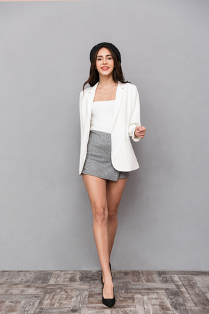Full length portrait of a beautiful young woman dressed in mini skirt and jacket walking over gray background, looking at camera