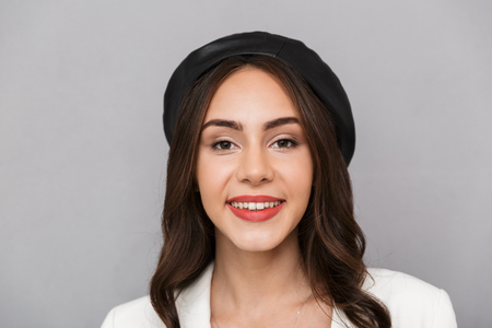 edb0b539f08 Close up portrait of a pretty young woman wearing beret standing isolated  over gray background