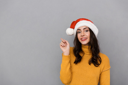 Portrait of happy woman wearing Santa Claus red hat smiling and pointing finger at copyspace isolated over gray background