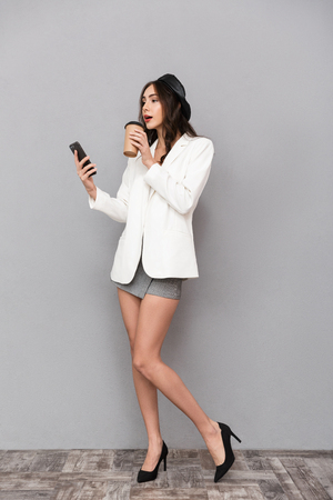 Full length portrait of a beautiful young woman dressed in mini skirt and jacket over gray background, drinking coffee, using mobile phone