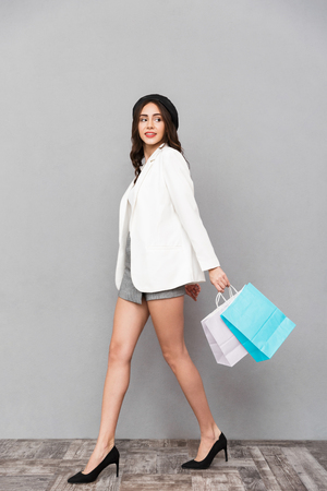 Full length portrait of a pretty young woman dressed in mini skirt and jacket over gray background, carrying shopping bags, walking