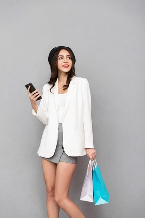 Portrait of a pretty young woman dressed in mini skirt and jacket over gray background, carrying shopping bags, using mobile phone Stock Photo