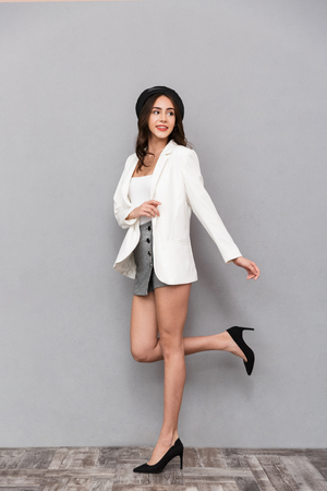 Full length portrait of a pretty young woman dressed in mini skirt and jacket walking over gray background, looking away