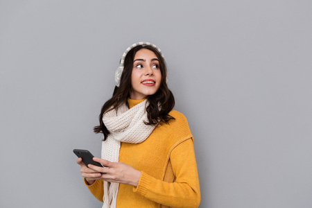 Portrait of brunette woman wearing ear muffs and scarf using mobile phone isolated over gray background