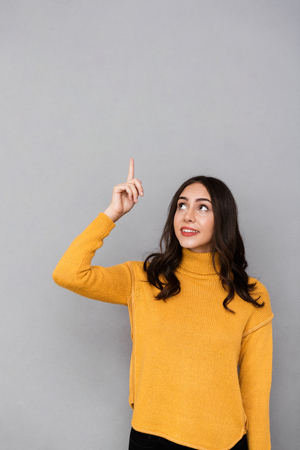 Image of pretty woman 30s with long dark hair looking and pointing finger upward isolated over gray background Stock Photo