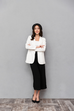 Full length portrait of a pretty young woman dressed in jacket and pants standing over gray background, looking at camera, arms folded
