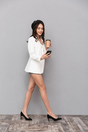 Full length portrait of a beautiful young woman dressed in mini skirt and jacket over gray background, holding cup of coffee, using mobile phone, walking